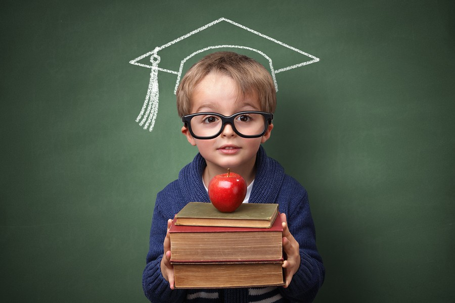 Child holding stack of books with mortar board chalk drawing on blackboard concept for university education and future aspirations